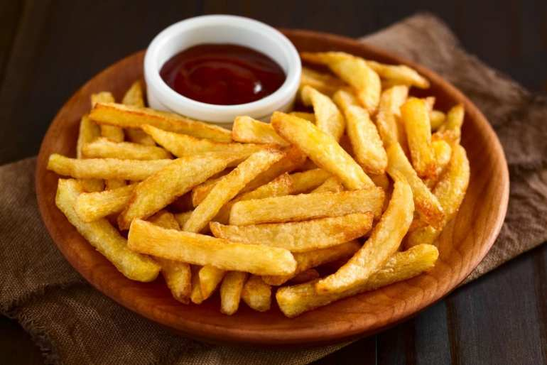 cannabis infused french fries on a wooden plate with ketchup beside them on the plate. All of this is on a napkin which is on a wooden table