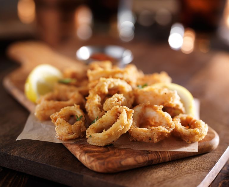 cannabis infused fried calamari rings on a wooden cutting board with a lime in the background out of focus