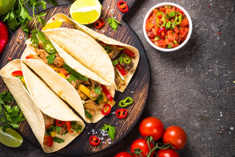 Overhead image of pork weed infused tacos Wooden cutting board and peppers and tomatoes and lime and lemon beside the tacos