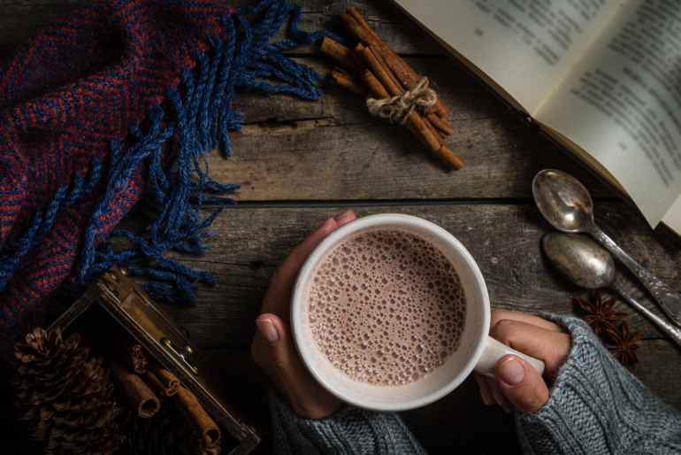 Overhead shot of a person hoding a cup of cannabis infused hot chocolate on a wood surface