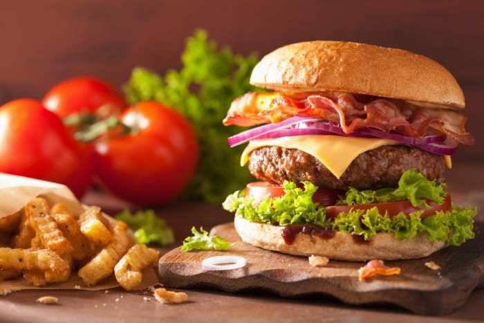 bacon weed cheese burger with beef patty tomato onion with french fries beside it on a wooden table