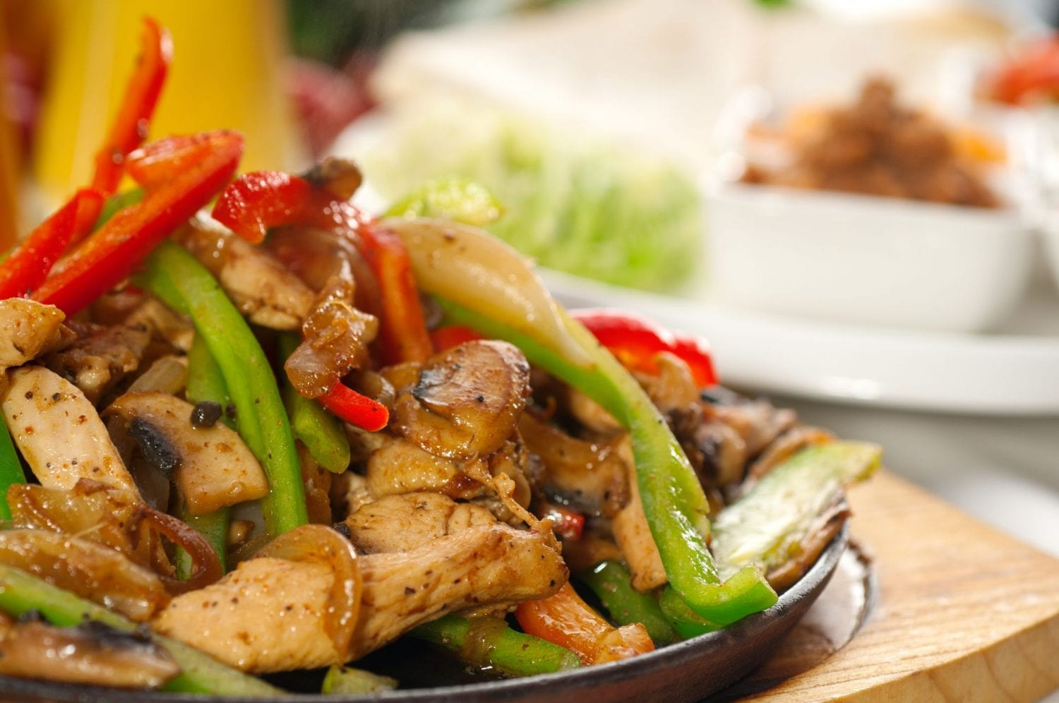 A hot pan with sizzling chicken green peppers red peppers and other veggies used for making weed fajitas