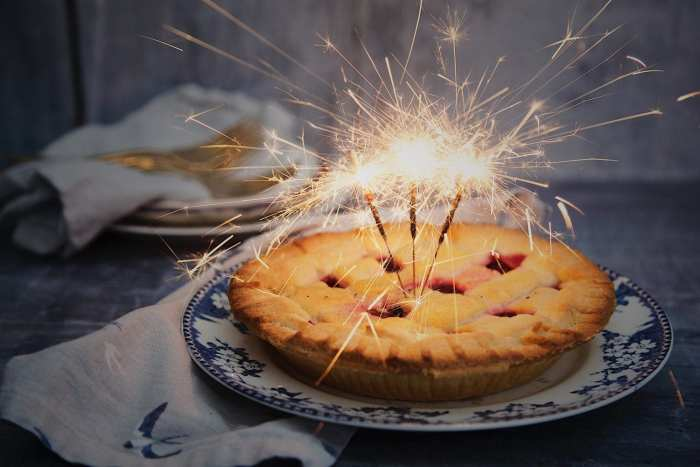 Edible apple pie with three sparklers sticking out the top of it all lit on fire the apple pie is on a blue plate