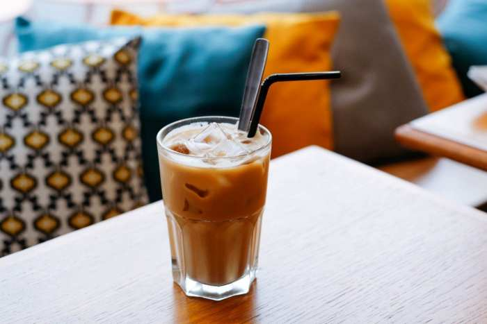 Infused iced coffee on a wooden table with pillows in the background