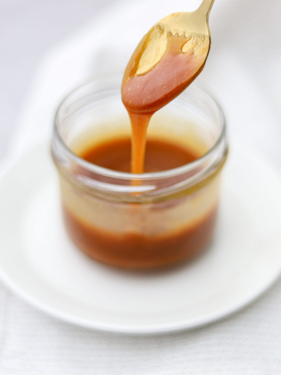 Cannabis infused caramel in a jar with a spoon scooping some of the caramel