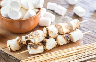 Cannabis infused Marshmallow skewers on the wooden board which is on a wooden surface with a bowl of weed marshmallows in the background