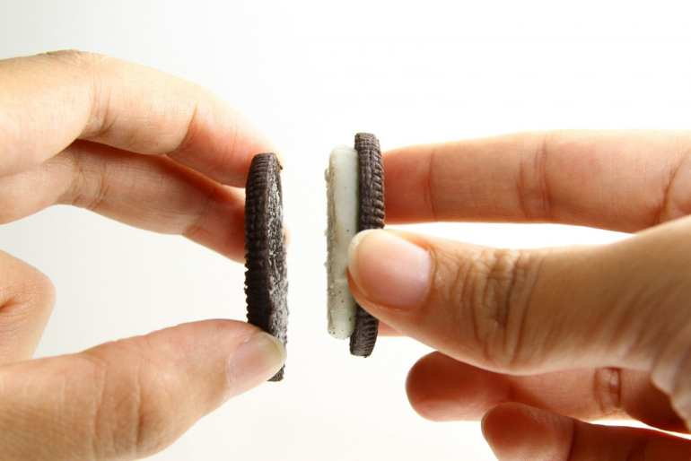A persons hands pulling an oreo in half separating the two sides of the cookie. a weed chocolate covered oreo recipe.