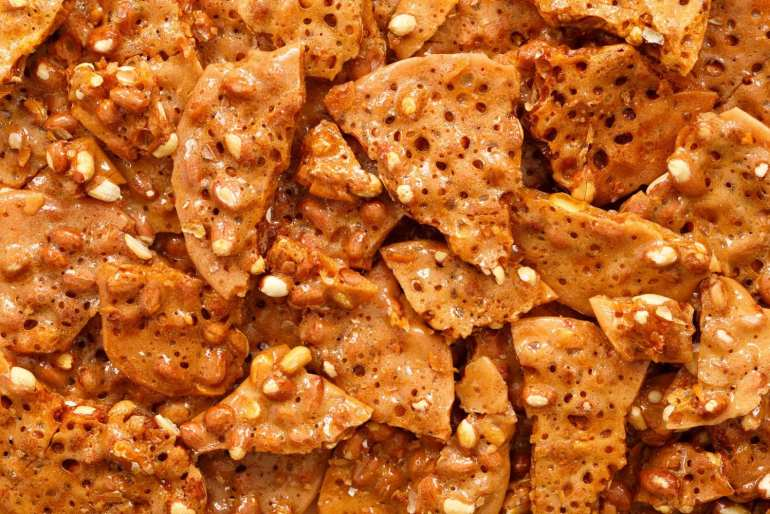 macro shot of a pile of cannabis infused peanut brittle stacked on top of eachother