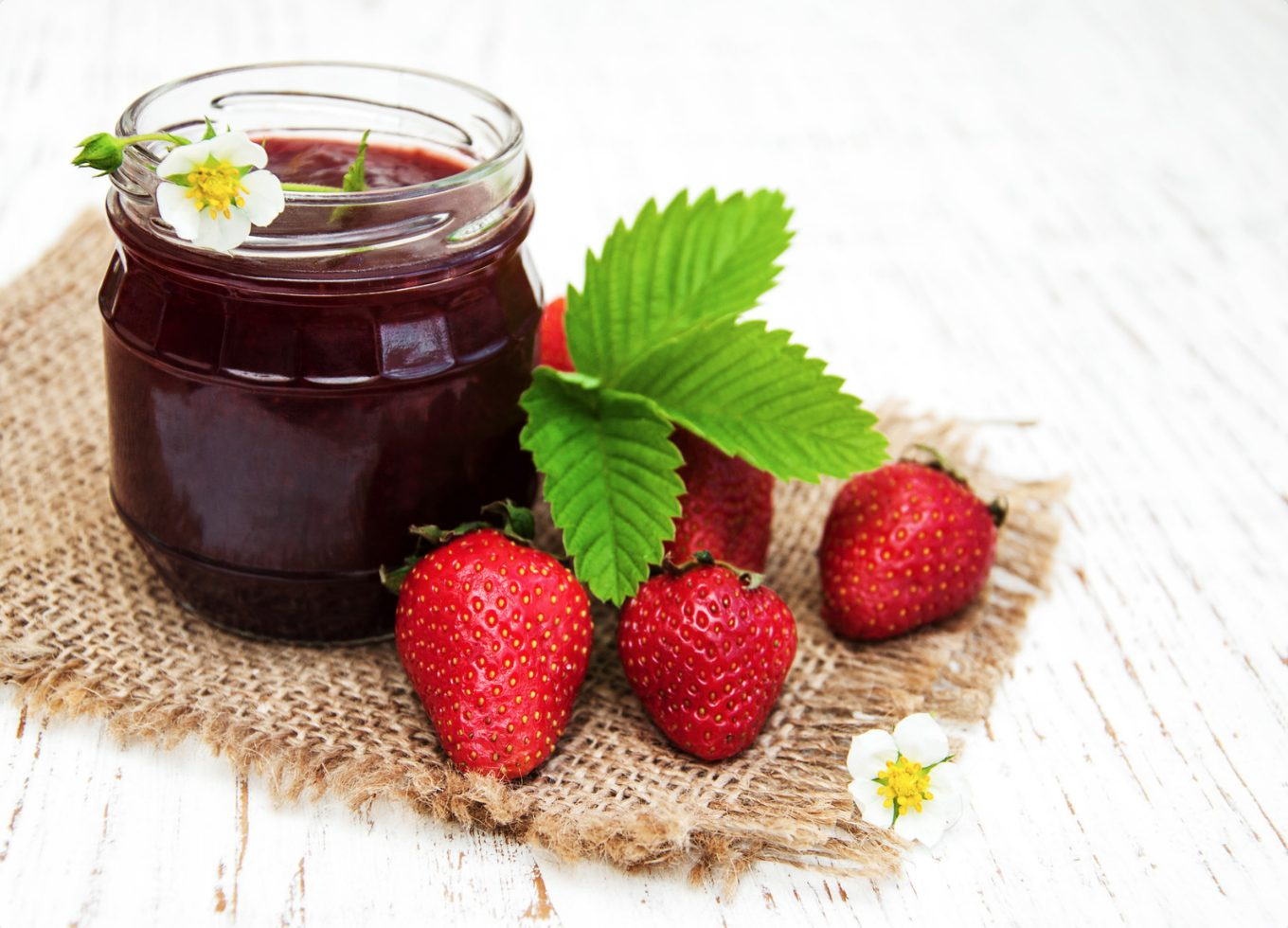 weed strawberry jam in a glass jar with strawberries beside the jar.