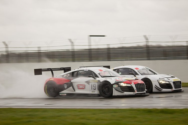 Two Audi R8s race in the rain.