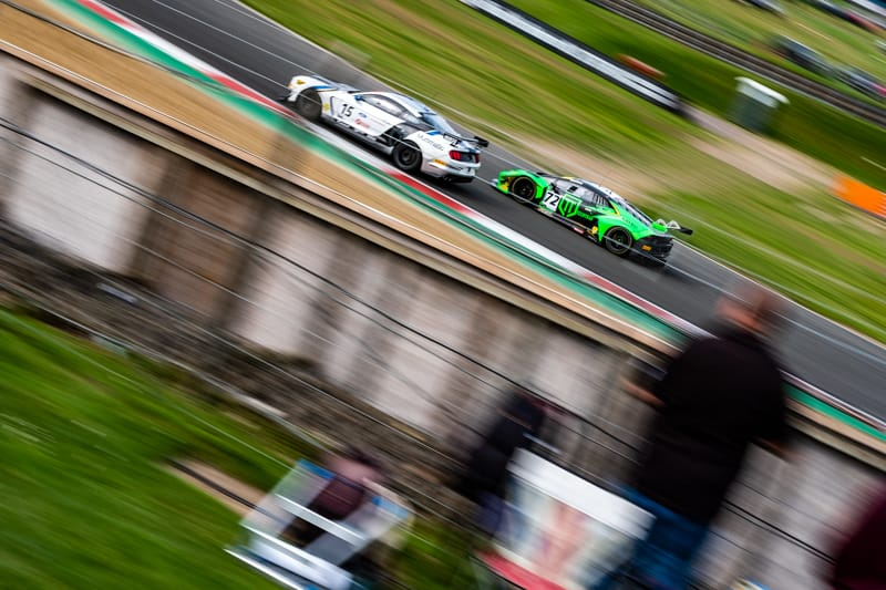 The #72 Barwell Motorsport Lamborghini Huracan GT3 EVO of Adam Balon and Phil Keen overtakes the #15 Ford Performance Mustang GT4 of Multimatic Motorsport's Seb Priaulx and Scott Maxwell at Paddock Hill Bend on the Brands Hatch GP Circuit.