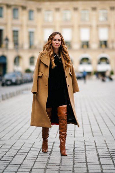 Abito nero, cuissardes e cappotto cammello