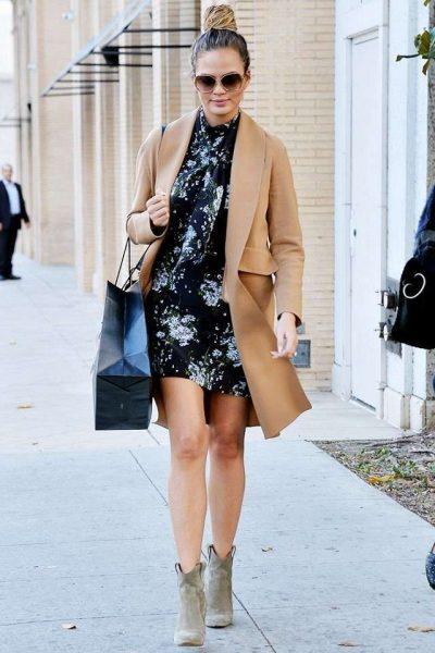 Chrissy Teigen indossa un cappotto cammello e un abito floreale