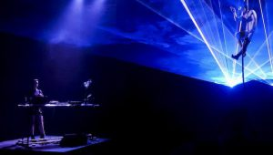 Photo of a very dark, indigo-tinged stage. In the bottom left of the image, musician Sue Zuki stands at a sparse desk of electronic equipment. In the top right of the image, aerialist Aedín Walsh supports herself up a vertical rope while shafts of bright white light laser past her, over Sue Zuki's head, and out towards us