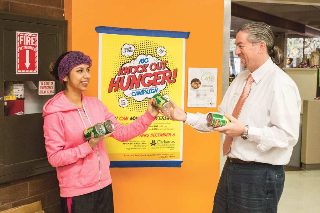 "Student Brenda Madrigal takes a few cans from the director of student leadership, John Ginsburg, to help ""knock out hunger."""