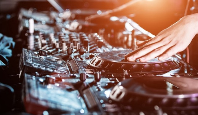 Dj mixes the track in the nightclub at party, close-up.