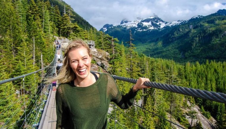 travel and reduce your carbon footprint; girl on suspension bridge canada
