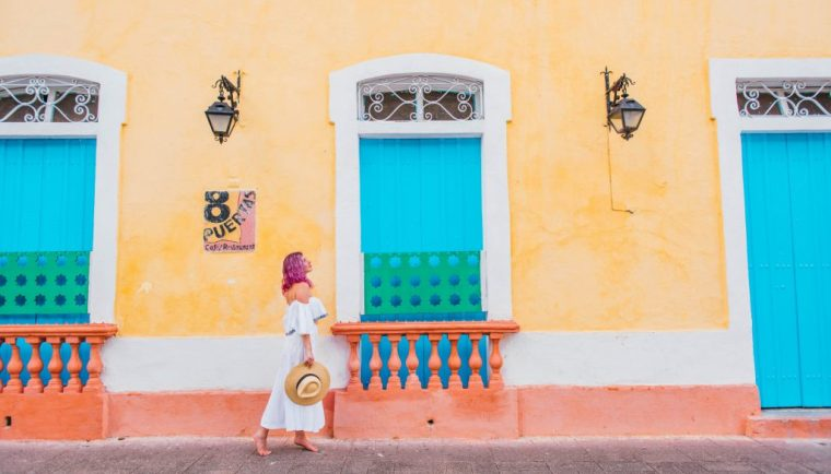 24 Hours in Santo Domingo; girl walking in front of yellow wall