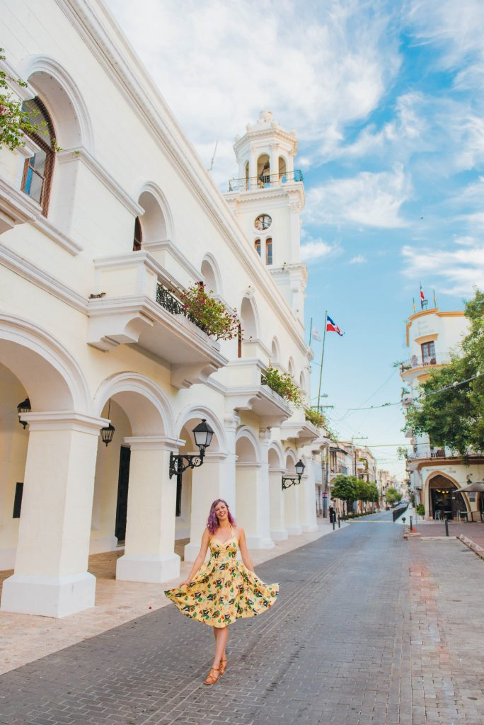 2017 was the best; girl walking in yellow dress in front of white building Santo Domingo Dominican Republic