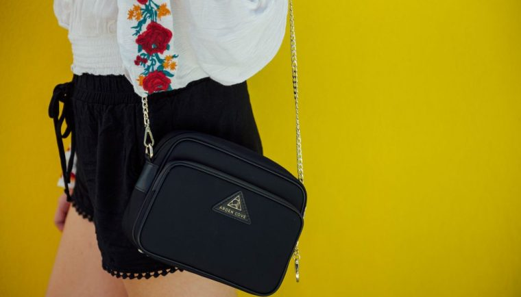 best anti theft purse; girl The Clumsy Traveler with black cross body bag Arden Cove close up