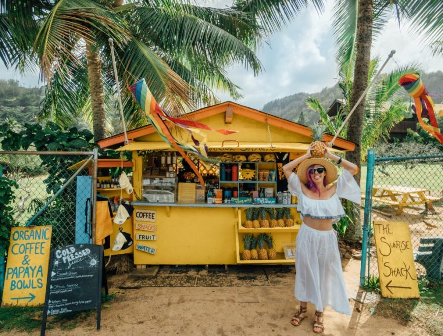 best things to do in Oahu; girl with pineapple at the Sunrise Shack yellow north shore