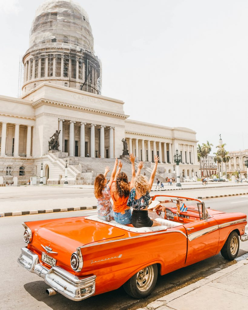 havana cuba photography; girls in red old convertible in parque central with el capitolio in the background