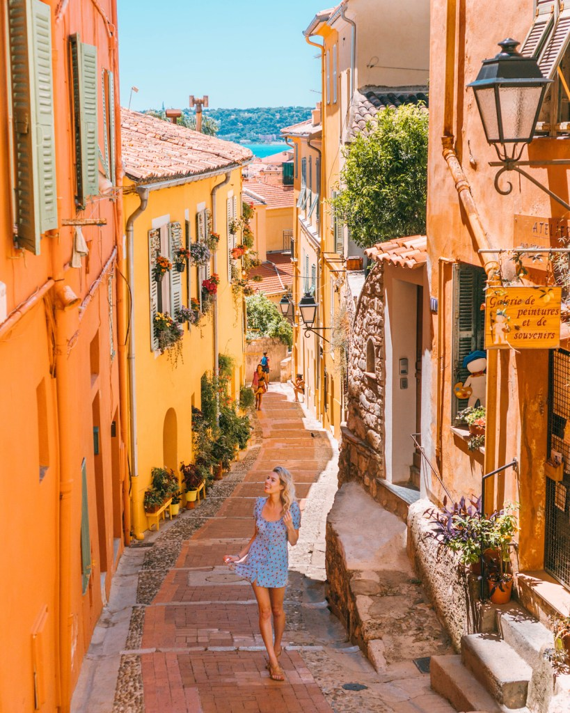 The Perfect 7-14 Day Provence and Côte d'Azur Itinerary; girl walking in blue dress in alleyways of Menton