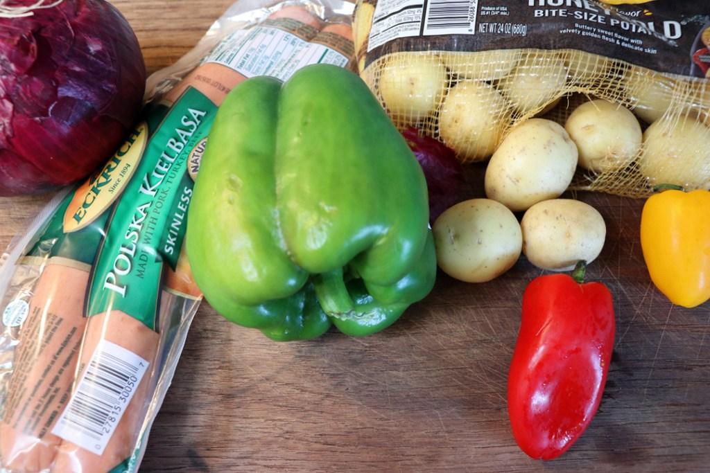 kielbasa, green pepper, red pepper, button potatoes, yellow pepper on a cutting board