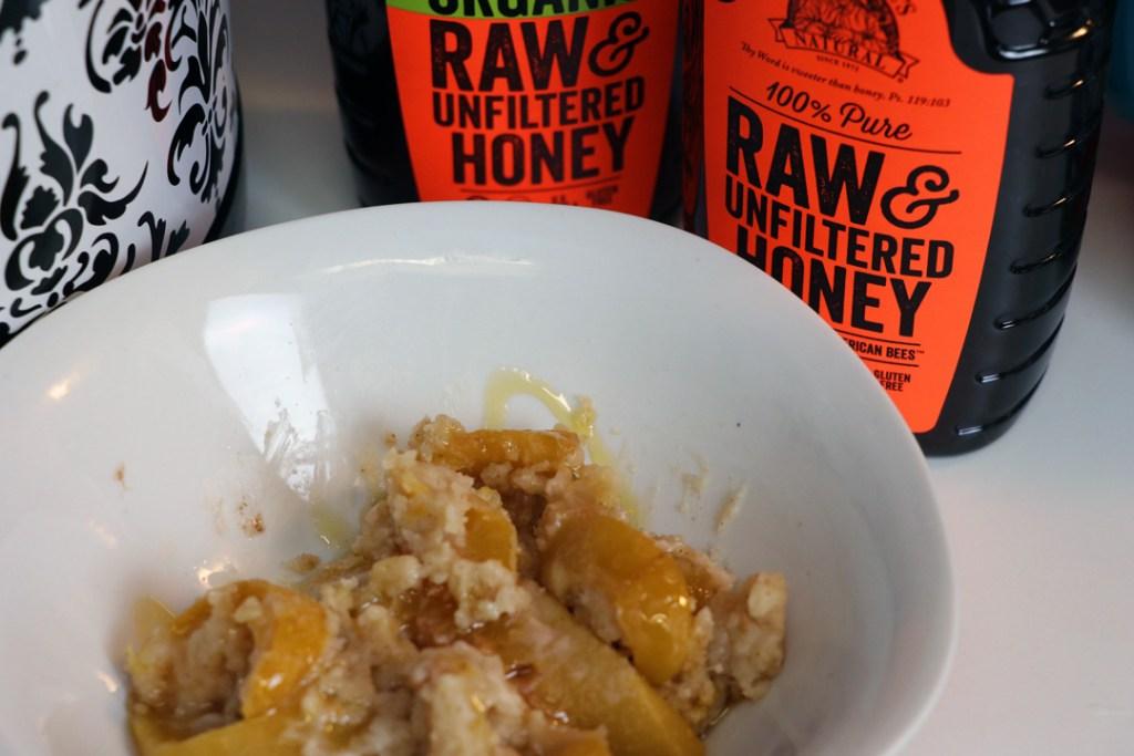 peach cobbler in a bowl next to honey