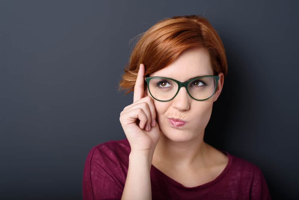 Nerdy scholastic young woman wearing geeky glasses standing thinking with her finger raised