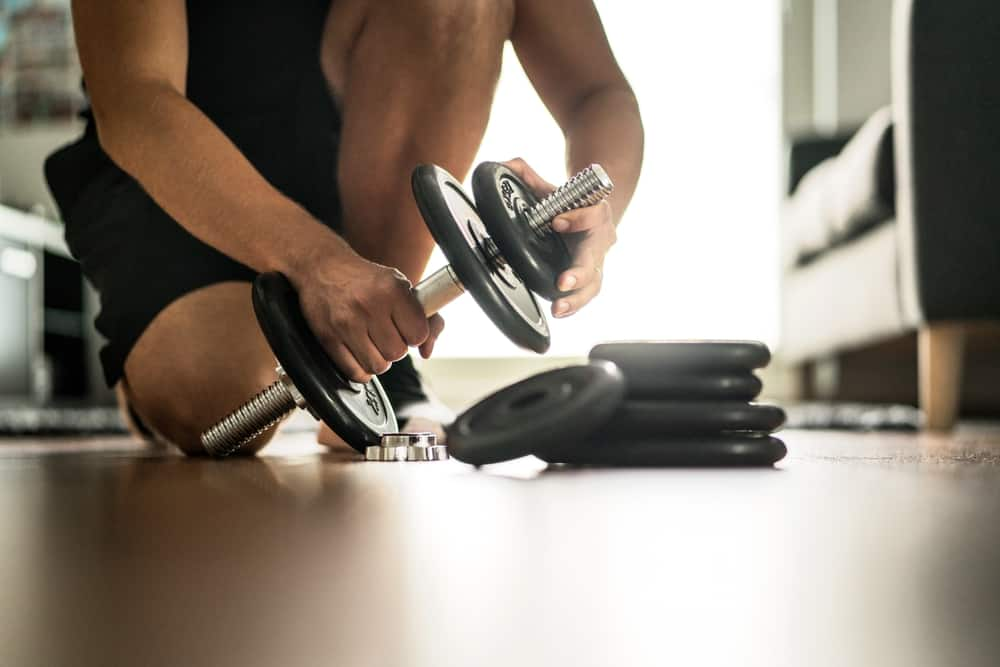 Man adding more weight to adjustable dumbbell in home gym