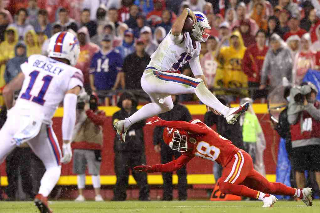 Josh Allen #17 of the Buffalo Bills leaps over the defense of L'Jarius Sneed #38 of the Kansas City Chiefs during the second half of a game at Arrowhead Stadium on October 10, 2021 in Kansas City, Missouri.