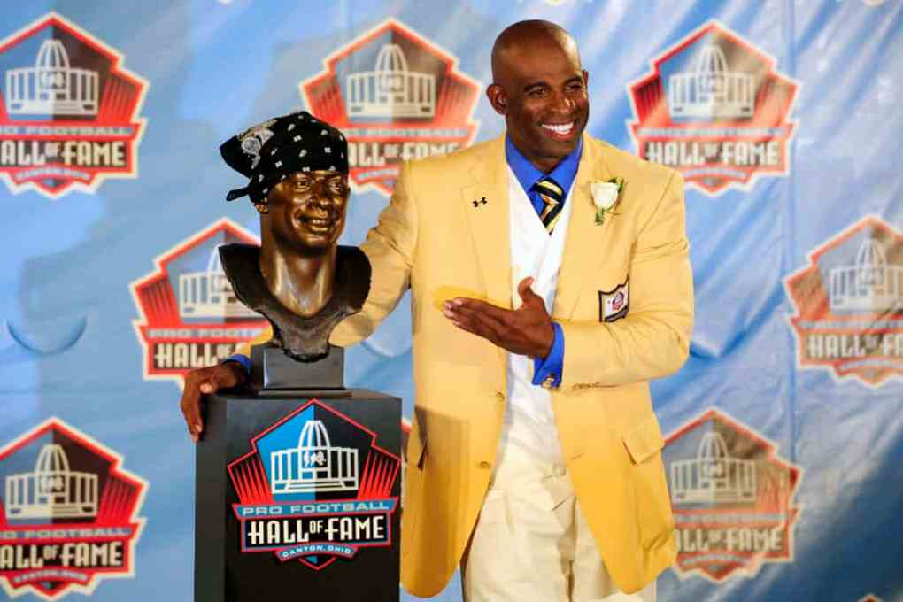 Former Atlanta Falcons cornerback Deion Sanders poses with his bust at the Enshrinement Ceremony for the Pro Football Hall of Fame on August 6, 2011 in Canton, Ohio.