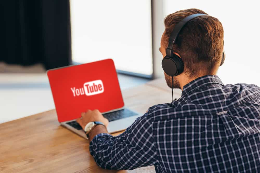 Partial view of man in headphones using laptop with youtube