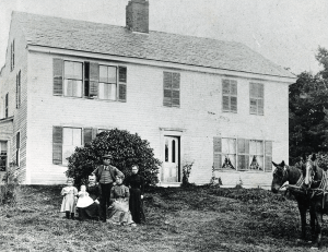 Family portrait in front of colonial home