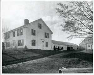 Side view of colonial house with stables