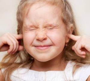 child with fingers in her ears
