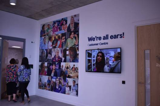 """Tesco room pictures on wall of people and """"we're all ears"""""""