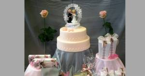 wedding cake groom and bride with white frill round them flower either side