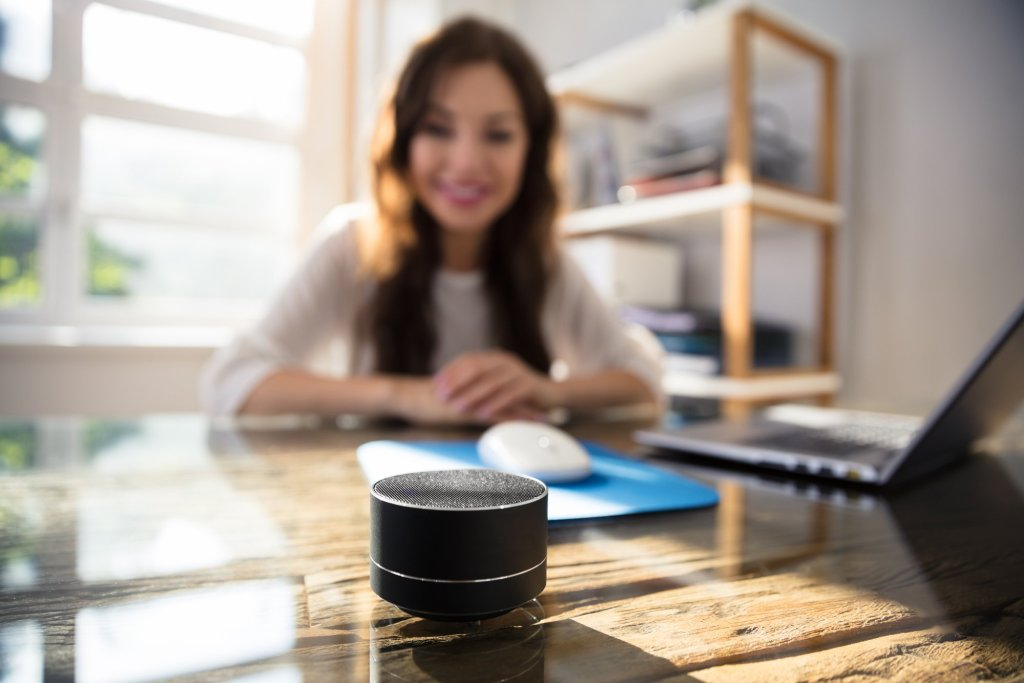 Healthcare provider listening to Alexa on smart speaker during meeting