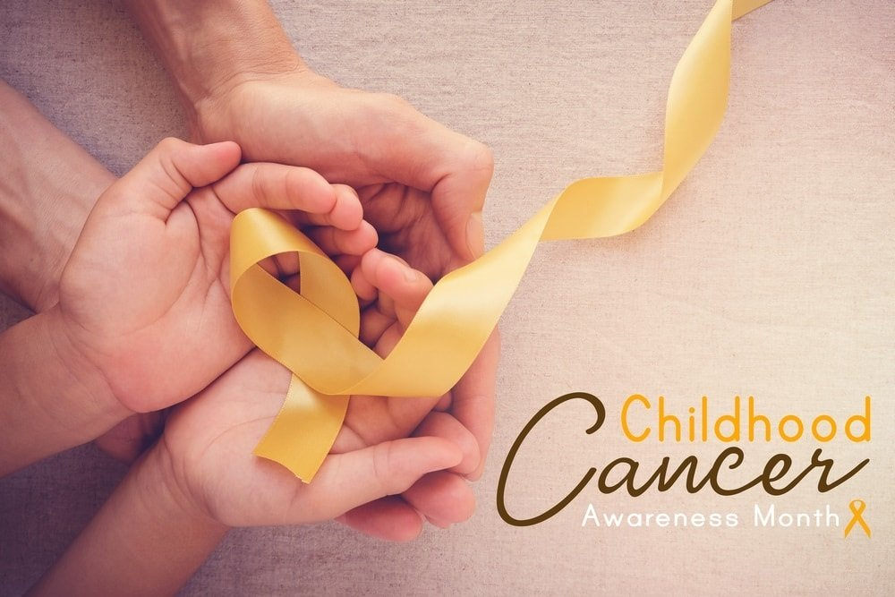 Childhood cancer awareness yellow ribbon held by child and dad