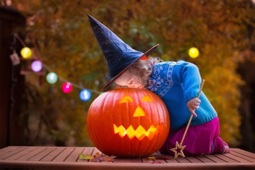 Young girl in witch's hat peering into carved pumpkin
