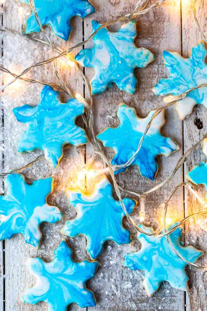 overhead view of blue snowflakes cookies intermixed with christmas lights