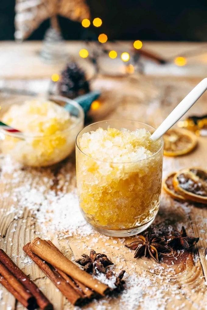 Glass of orange bourbon slush with a white spoon