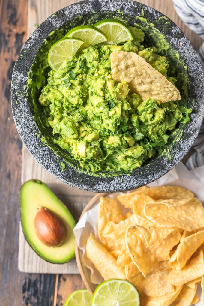 Simple guacamole dip next to a basket of tortilla chips