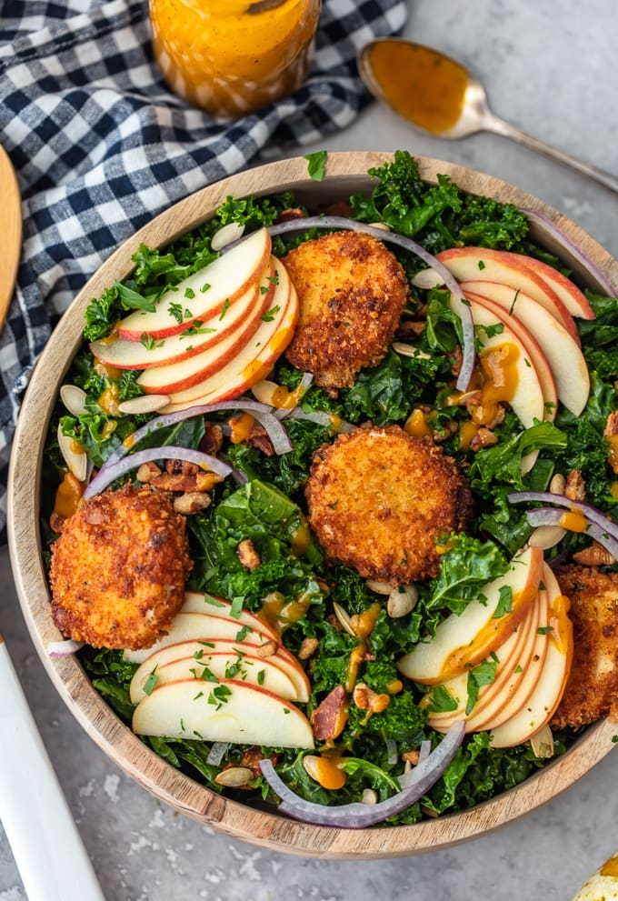 Autumn salad made with kale, apple slices, onions, fried goat cheese, and maple pumpkin salad dressing