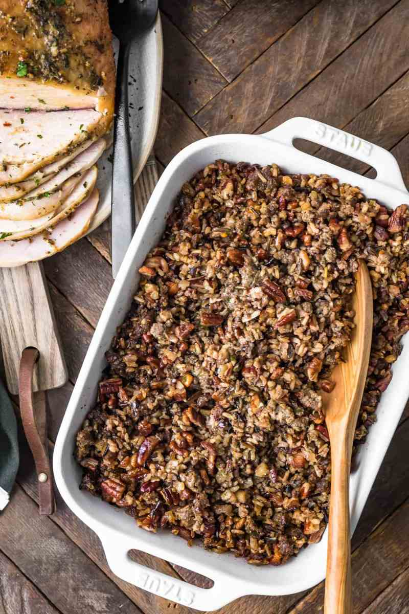 Wild Rice Sausage Stuffing in a dish with a wooden spoon