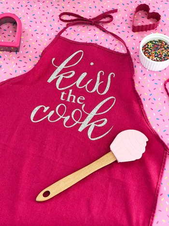 Make this DIY kiss the cook apron as a gift or for yourself!  It is super easy with a Cricut machine and iron-on vinyl!
