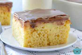 Boston Cream Poke Cake, slice on a white plate with a glass of milk in background