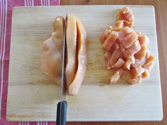 slicing boneless skinless chicken breasts on a wooden cutting board